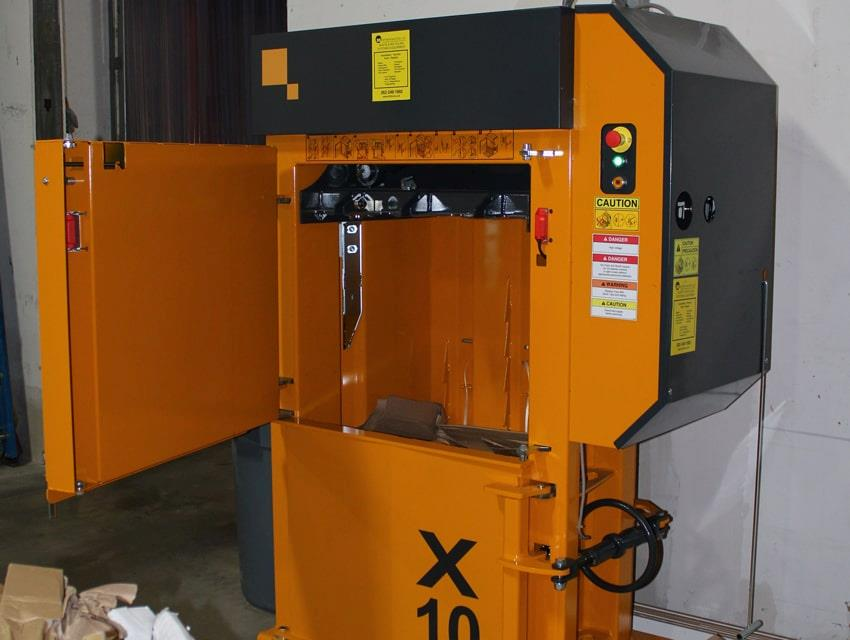 Door open into chamber of yellow Bramidan baler X10
