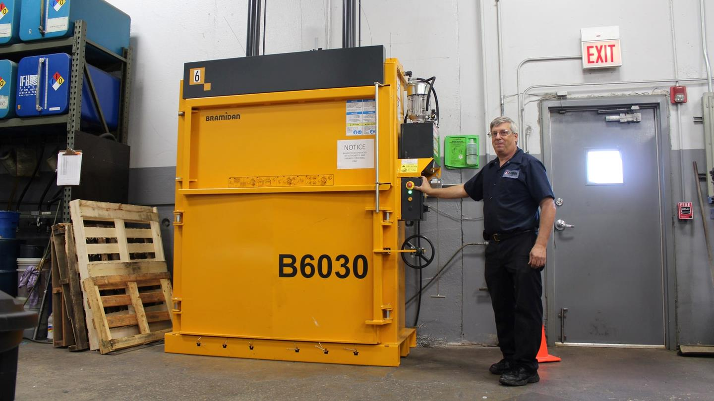 Man pushes start botton of B30 Wide vertical baler